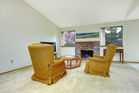 Birght living room with brick background fireplace, glass coffee table , tv, antique mustard armchairs and table photo