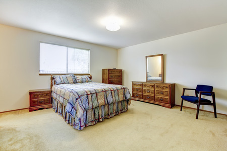 nightstands: Spacious bedroom with window and beige carpet floor. Furnished with carved wood bed, nightstands and dresser with mirror Stock Photo