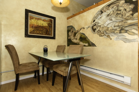 Glass top dining table with chairs  View of beautifully painted wall  Mikelandjelo work reproduction