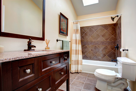 Ivory bathroom with chocolate color vanity, white toilet, tub with tile wall trim and pleated curtain