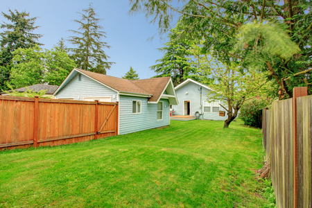fenced: Fenced side yard with green lawn, View of the back yard deck