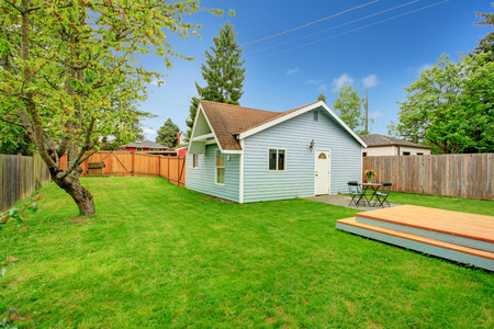 fenced: View of siding house with fenced backyard, View of green lawn, small concrete floor patio area with table set