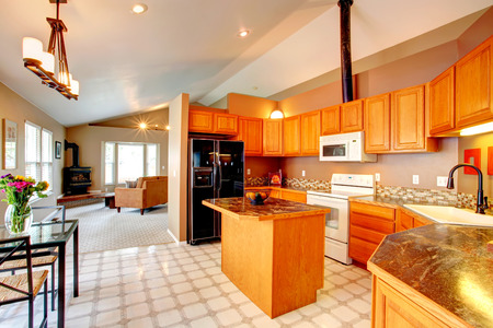 Spacious kitchen room with vaulted ceiling and lenoleum floor  VIew of kitchen gold cabinets, island and black refrigerator photo