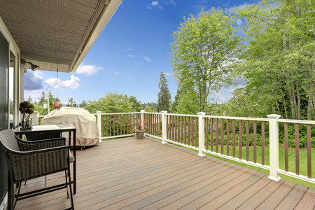 Wooden deck with white and brown railings  Patio table with wicker chairs and barbeque