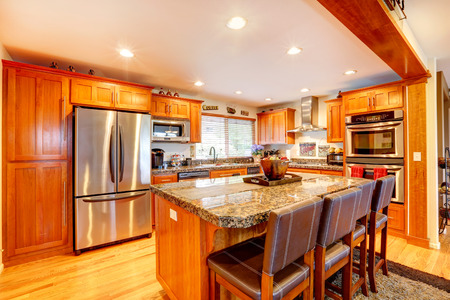 Kitchen with honey color cabinets, steel appliances  View  of island with marble counter top and leather stools Stock Photo - 26812802