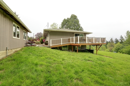 House with white and brown walkout deck  View of green lawn Stock Photo - 26812805