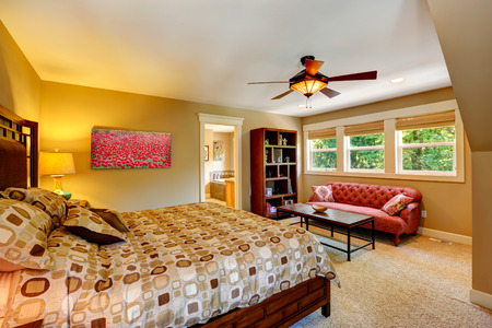 master bedroom: Beautiful bedroom with queen size bed and antique red couch. View of the bedroom corner Stock Photo
