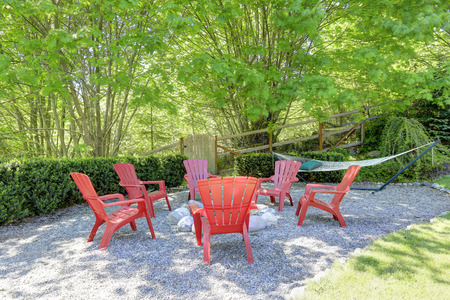 Green beautiful backyard with rest area. Red wooden chairs with fire pit and hamaque
