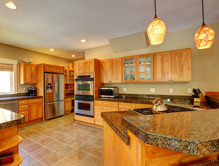 Spacious kitchen room with tile floor, wood cabinets and steel appliances Stock Photo