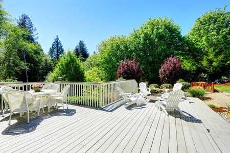 Beautiful backyard deck with white wicker table set, fire pit and chairs. photo
