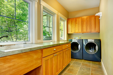 Narrow laundry room with wooden cabinets, washer and dryer photo