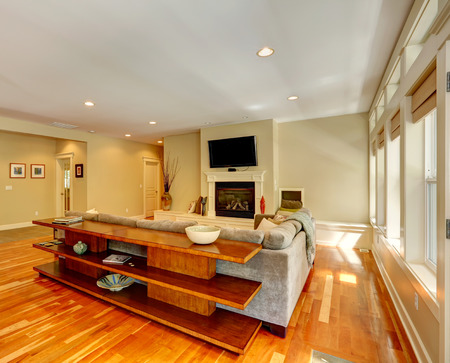 Luxury living room with fireplace and TV. View of couch and three level table set behind ше photo