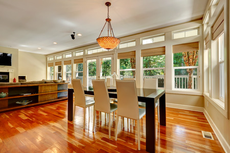 Spacious living room with walkout deck  View of elegant white and black dining table set photo