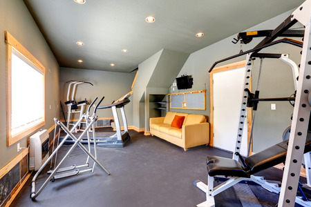 home gym: Grey walls gym room with window  View of exercise equipments and yellow couch