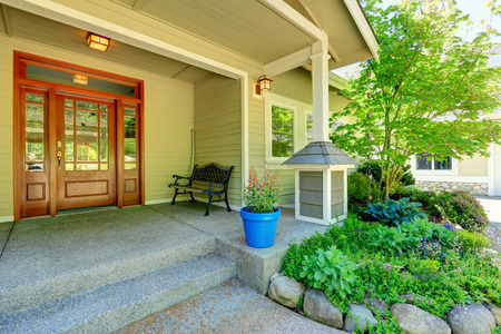 View of porch with entrance door, antique bench and flower bed Фото со стока