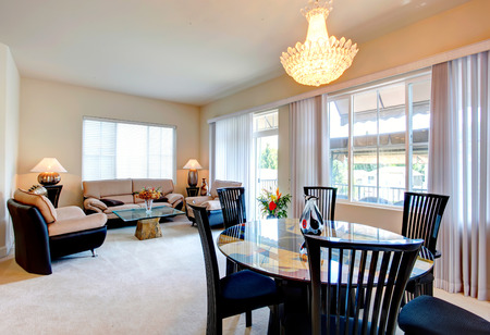 Bright living room with elegant leather furniture set, glass top coffee table and dining table set photo