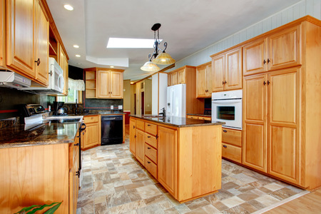 vaulted: View of kitchen with tile floor and vaulted ceiling  Furnished with cabinets,  island with sink and white appliances