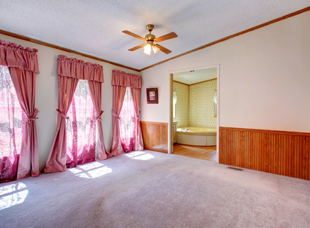 Empty master bedroom with open door to bathroom  View of window treament with pink curtains photo