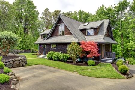 녹색 잔디와 놀라운 피는 나무 Clapbord 사이딩 갈색의 집은 도로에서보기