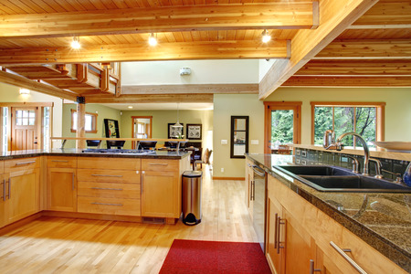 log cabin: View of kitchen cabinets, ceiling beams and hardwood floor with red rug