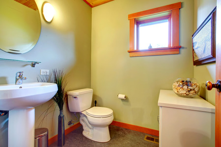 Bright bathroom with small window  View of white basinstand, toilet and simple cabinet with shells in vase photo