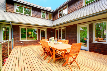 house siding: Clapbord siding brown house with wooden deck  View of served rustic table with chairs Stock Photo