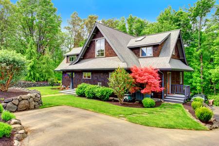 Clapbord opruimen bruine huis met groene gazon en prachtige bloeiende bomen Uitzicht vanaf de oprit Stockfoto