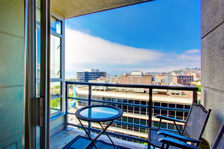 balcony: Apartment balcony with glass top table and wicker chairs. Balcony overlooking city panoramic view Stock Photo