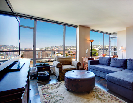city living: Modern apartment with amazing city view through the glass wall. Stock Photo