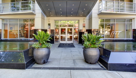 luxury apartment: Modern and shiny residential apartments building with glass entrance door and walkway. Two big pots with flowers along side the walkway Stock Photo
