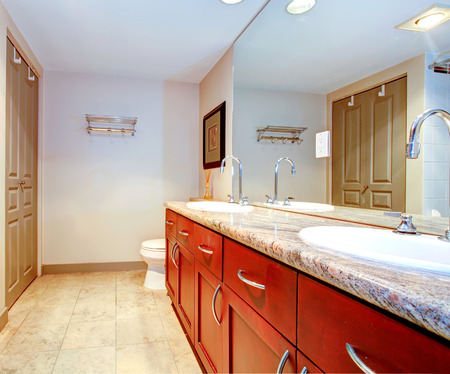 Bathroom with brown cabinets with two sinks  View of bath tub corner