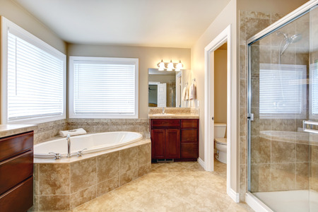 Beige bathroom with windows, cherry wooden cabinets, glass door shower and toilet. View of round white bath tub Banco de Imagens