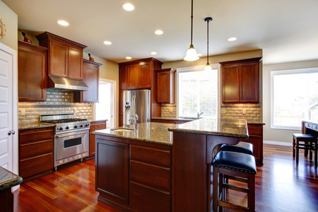 Beautiful kitchen room with oak cabinets, steel appliances  View bar counter with black chairs  photo