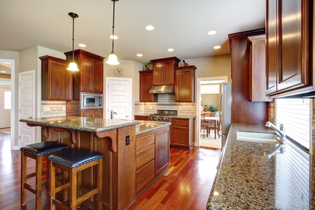 cabinets: Beautiful kitchen room with oak cabinets, steel appliances  View bar counter with black chairs
