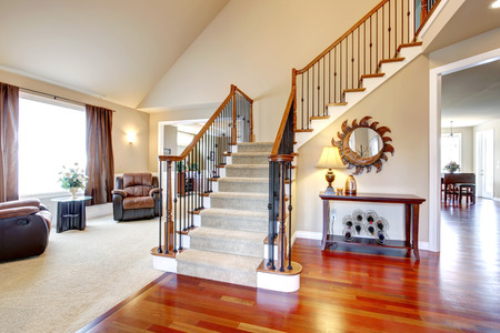 堅木張りの階段と廊下と革張りのアームチェアとテーブル付きのリビング ルームのビュー