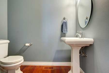 bathroom mirror: Simple grey bathroom  VIew of white toilet and washstand Stock Photo