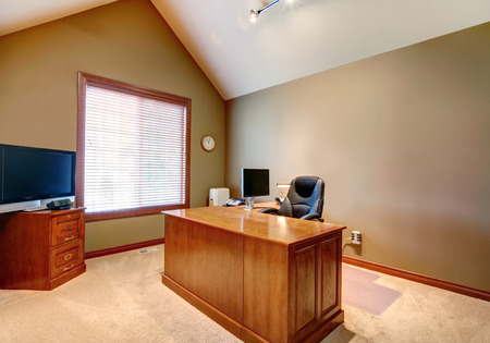 Furnished office room with olive walls, white high vaulted ceiling  View of oak desk with chair and TV on the cabinet Stock Photo - 27139603