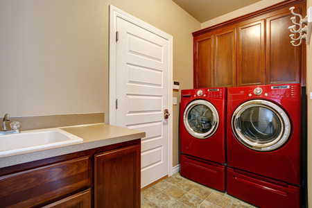 laundry room: Laundry room with wooden storage cabinets, modern red washer and dryer