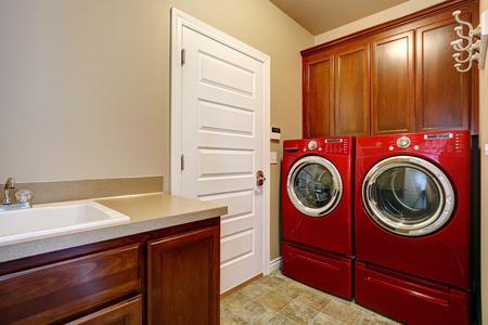 machine � laver: Salle de lavage avec armoires de rangement en bois, vaisselle moderne rouge et s�che