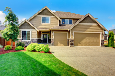 house siding: Beige luxury house tih stone trim base  View of porch, garage and driveway Stock Photo