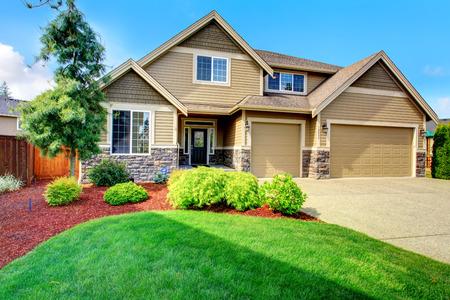 Clapboard gevelbeplating huis met stenen bekleding Uitzicht op entree veranda, mooie bloem bed met groene gazon, struiken en spar