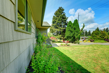 house siding: Clapboard siding house with flower bed. Close up view of wall with window
