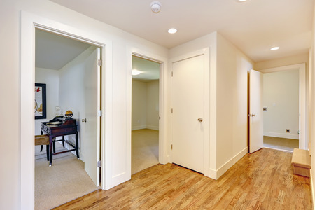 Empty hallway with hardwood floor, white walls. View of other room from the corridor photo