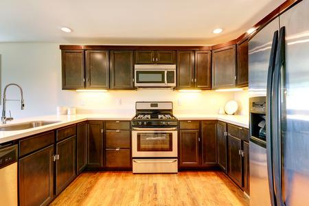 appliances: Dark brown kitchen room with steel appliances.