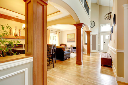 light columns: Spacious high ceiling house with wooden column in it. View of hallway with ottoman, living area and entrance door. Stock Photo