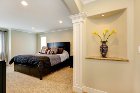 niche: View of elegant black bedroom furniture and niche in the wall decorated with polka dot vase and yellow flowers