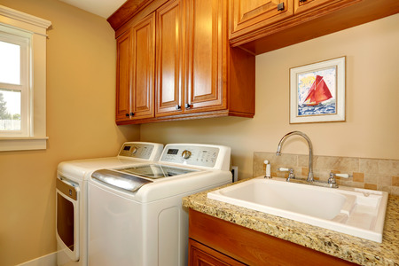 Laundry room with cabinets and whire appliances. photo