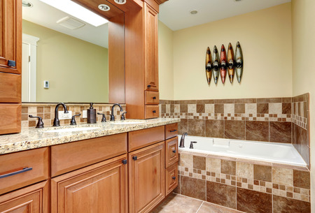 Bathroom with close up view of cabinets with mirror and bath tub with tile wall trim and candles photo