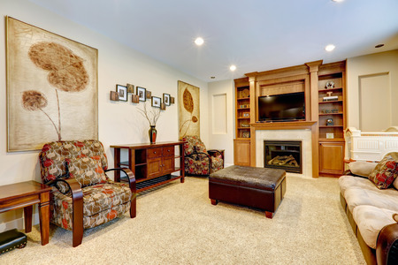 Furnished luxury living room with leather ottaman  View of fireplace with tv and built-in cabinet photo