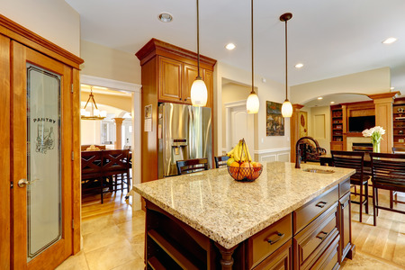 Luxury kitchen with light brown  cabinets, steel appliances, pantry, marble counter top island photo